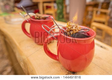 German drink, hot wine and flaming sugar - Image with a mug of hot wine which has tongs with a flaming cone of sugar on top. It is a traditional german drink at Christmas fairs called