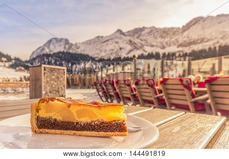 Fruit cake served at a restaurant in the mountains - Close-up image with a delicious cake with cocoa batter vanilla filling and fruits served on a sunny winter day in the Austrian Alps mountains.