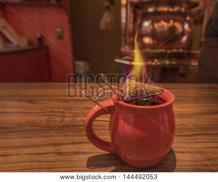Hot drink, mulled wine and burning sugar - Close-up image with a cup of mulled wine on top of which stands a burning cone of brown sugar previously dipped in a lot of rum. This is a traditional german Christmas drink called