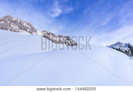 Large piles of snow - Lovely winter background with big piles of snow surrounded by the peaks of the Austrian Alps mountains under a blue sky.