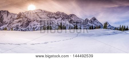 Mountain peaks with footsteps on snow - Winter landscape with Austrian alps peaks a single trail of footsteps on snow under a dramatic and colorful sky.