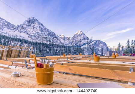 Outdoor restaurant in the mountains - Image with the terrace of a restaurant surrounded by the Alps mountains with the rustic wooden tables ready to receive the guests.
