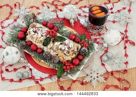 Christmas stollen cake, mulled wine cocktail, holly, fir, red, silver and white bauble decorations with glitter snowflakes.