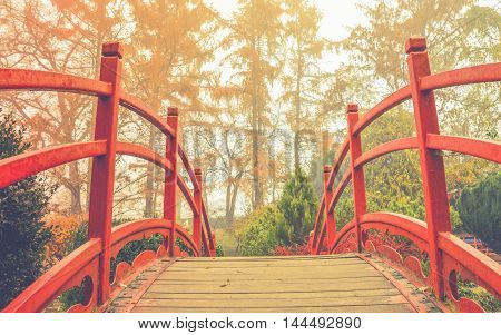 Red wooden bridge in soft light   - Wooden bridge with the red handrails in a japanese garden against a background of autumnal trees.