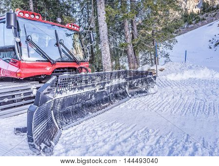 Snow groomer machine, front view - Front image of a piste machine a red snow groomer with details on the blade tiller and cabin.