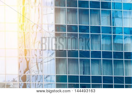Fragment of the glass facade in the business building with sunflare effect