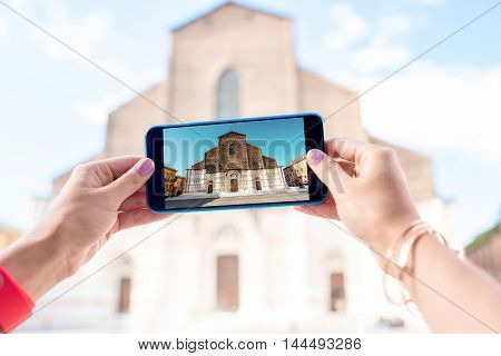 Photographing with phone San Petronio church on the main square in Bologna city.