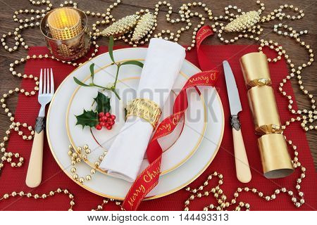 Luxury christmas dinner table setting with white plates, antique cutlery, linen serviette, holly, mistletoe, gold bauble decorations, candle, ribbon and cracker on red place mat over oak background.