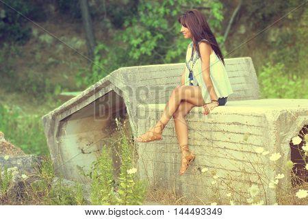 Beautiful young woman sitting on a stone