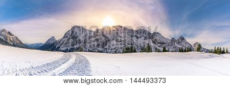Sunny winter day in the mountains - Alpine panorama with the Austrian Alps mountains from the Ehrwald municipality the green coniferous trees and a thick layer of snow over its pastures. A gorgeous winter sun overwhelms the entire scene.
