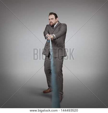 Businessman pulling rope at office - studio shot