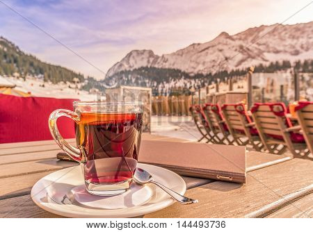 Warm drink and restaurant menu on table in alpine decor - Image with a hot drink and a restaurant menu on a wooden table on a sunny winter day mountains in the background. Picture taken in Austria.