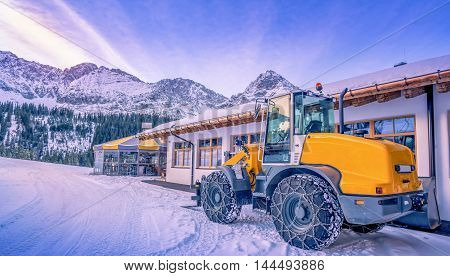 Wheel loader winter adapted - A yellow wheel loader with chains on its tires ready to remove the snow from the mountain paths. A lovely winter scenery from the austrian Alps
