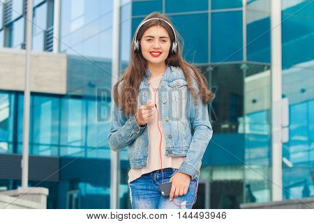 Beautiful girl listening music in headphones and standing on a colorful blue background . She has a beautiful smile .The concept of good music and fun