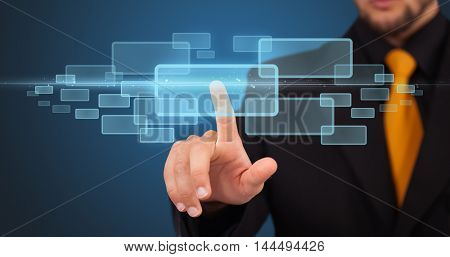 Businessman pressing high tech type of modern buttons on a virtual background