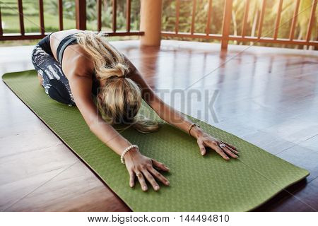 Young woman doing stretching workout on fitness mat. Female performing yoga on exercise mat at gym. Child Pose Balasana.
