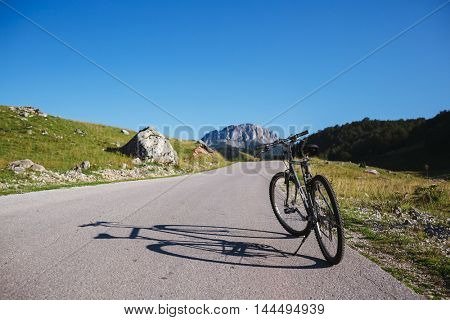 Bicycle Parked On Road Leading Towards Green Mountains