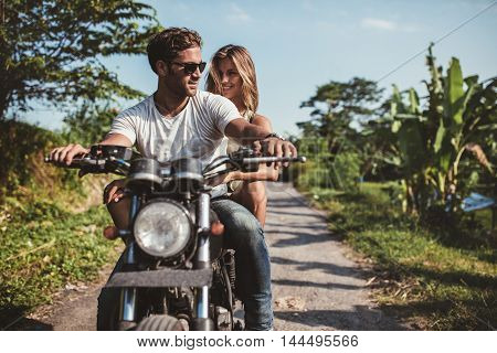 Man Riding On A Motorbike With Girlfriend On Country Road