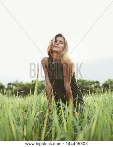 Attractive Young Lady Sitting In The Field