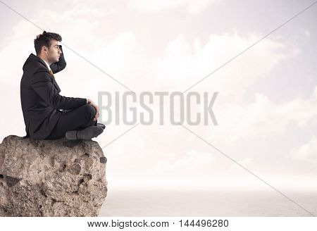 A young sales person in elegant suit sitting with paper on top of a stone in the clouds concept