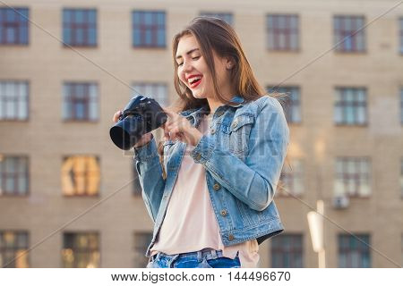 Young beautiful girl photographs . She is dressed in a denim suit . It portrait lens . Photography and creativity