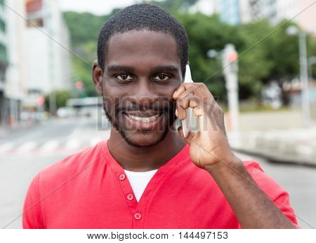 African american man with red shirt at phone in modern city