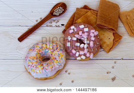 pretty tasty donuts on white wooden background with sweets and wooden utensils