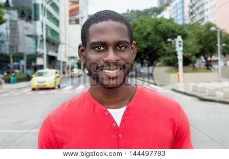 Laughing african american man with red shirt in modern city