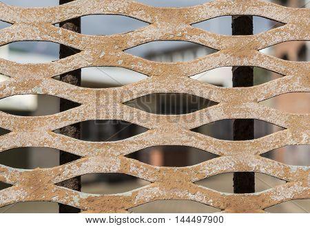 Abstract view looking through a peeling rusting old metal door grate.
