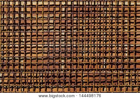Abstract Patterns created by rusting woven metal mesh screen in front of a solid brick wall.