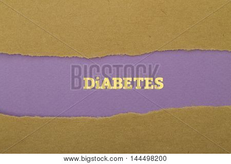 Diabetes word written under torn paper .
