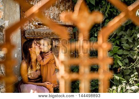 mother and daughter embrace, emotions on the background of wooden old door