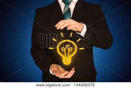 A creative businessman has a great bright idea illustrated by holding a drawn light bulb in the hand concept