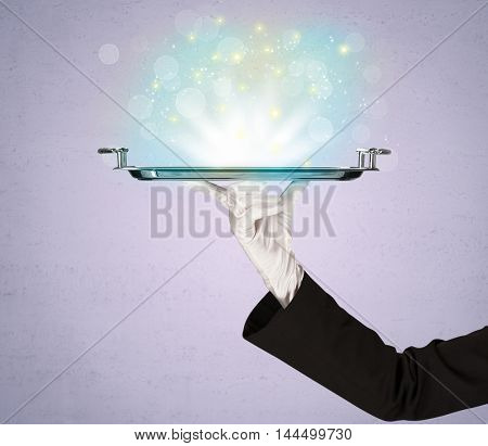 Glowing lights glitter on silver plate served on tray by waiter hand in white elegant glove in front of purple background