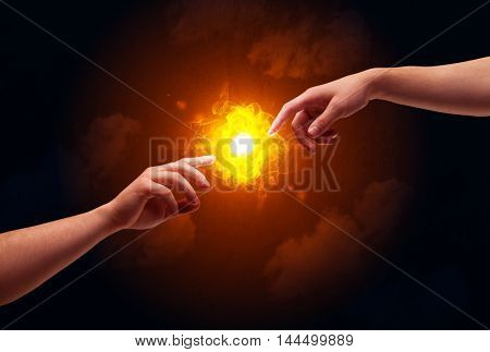 Two naked male hands about to touch, lighting a bright flame with smoke in red sky background concept