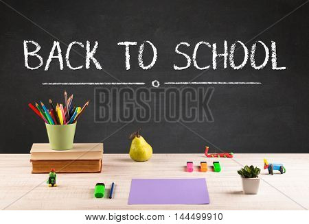Back to school concept with writing on blackboard in capital letters and a desk with papers, fruit