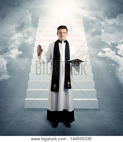 A young religious happy priest standing in front of the stairway to heaven concept with clouds and bright lights coming from above.