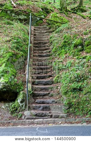 in the forest in Luxembourg there is a stone staircase with a handrail