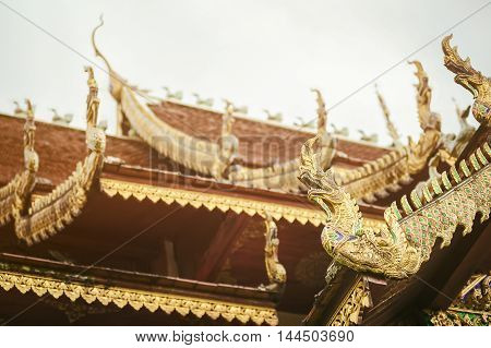Thailand art and architecture: Naga wood carved on roof at Thai temple.