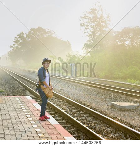 In a foggy sunshine day an asian women travelers waiting for a train on the platform at local Train Station.