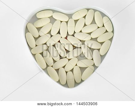 Yellow pills In a heart-shaped box, isolated on the white background.