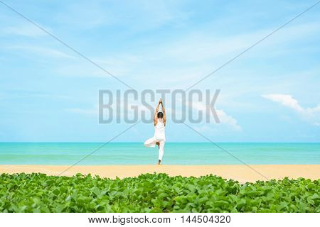 a man practicing yoga on the beautiful beach and tropical seashore Ipomoea foreground.