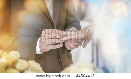 The groom was wearing a wedding ring to the bride at the wedding.