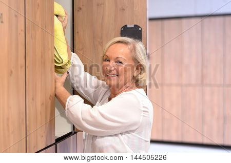 Attractive Senior Woman Reaching Into A Cupboard