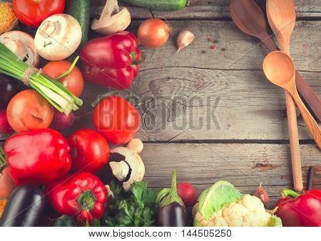 Healthy Organic Vegetables on Wooden Background. Frame of vegan food on wood. Space for your text