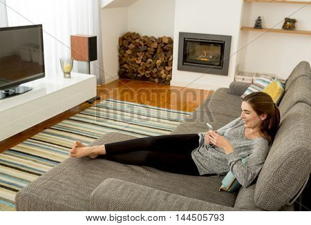 Beautiful woman at home sending text messages