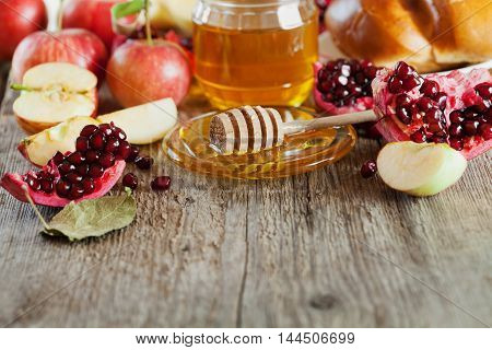 Table set with traditional food for Jewish New Year Holiday Rosh Hashana: honey, apple, pomegranate and hala