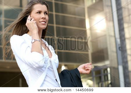 Young attractive businesswoman walking along the street
