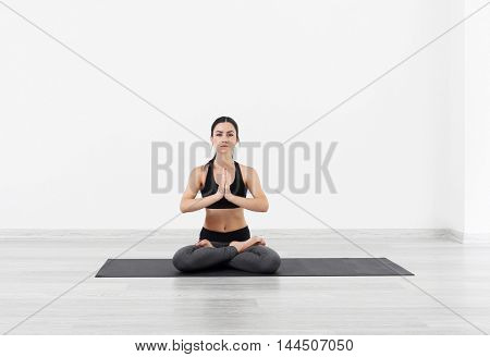 Young girl doing yoga exercises in light room