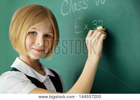 Cute schoolgirl writing on chalkboard